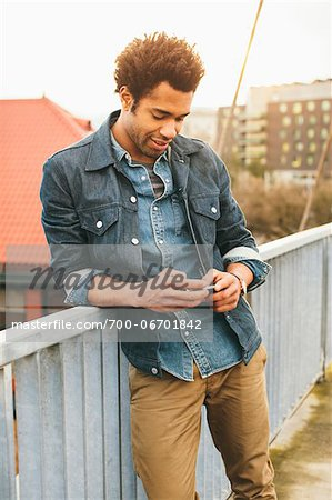 Young man texting on an iPhone in an urban setting. Stock Photo - Rights-Managed, Image code: 700-06701842