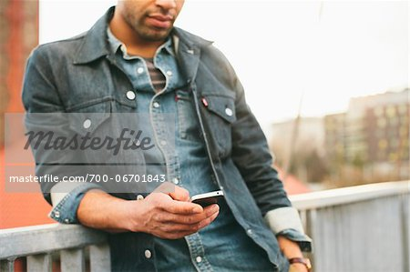 Close-up of young man texting on an iPhone in an urban setting. Stock Photo - Rights-Managed, Image code: 700-06701843