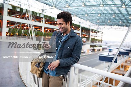 Smiling Man Texting on Cell Phone at the Airport Stock Photo - Rights-Managed, Image code: 700-06701846