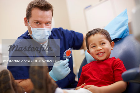 Dentist and young patient smiling after checkup examination. The dentist is handing a lollipop to the young male patient. Both subjects are smiling toward the camera. Stock Photo - Rights-Managed, Image code: 700-06786927