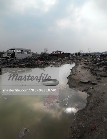 Tire floating in puddle in burnt out wasteland, Saint Denis, France Stock Photo - Rights-Managed, Image code: 700-06808740