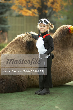 Girl in panda halloween costume standing next to camel Stock Photo - Rights-Managed, Image code: 700-06808831
