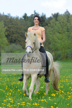 Young woman riding a icelandic horse on a meadow in spring, Germany Stock Photo - Rights-Managed, Image code: 700-06808856