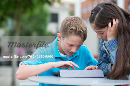 Boy and girl playing on an iPad outside. Stock Photo - Rights-Managed, Image code: 700-06808960