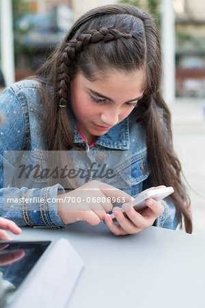 Girl using an iPhone 5 in urban park Stock Photo - Rights-Managed, Image code: 700-06808963