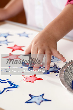 Close-up of child's hand stamping star-shapes in paint on a sheet of paper Stock Photo - Rights-Managed, Image code: 700-06895096