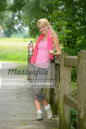 Portrait of blond woman wearing exercise clothing and holding bottle of water outdoors, Germany Stock Photo - Rights-Managed, Image code: 700-06899963
