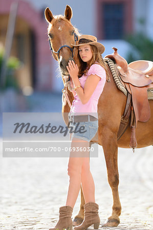 Young attractive woman standing beside a horse at a castle forecourt, Germany Stock Photo - Rights-Managed, Image code: 700-06936030
