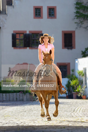 Young attractive woman riding a horse at a castle forecourt, Germany Stock Photo - Rights-Managed, Image code: 700-06936032