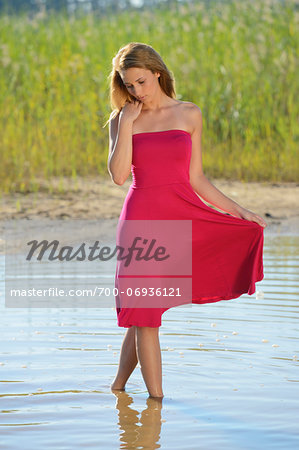 Young woman on a beach next to a little lake, Bavaria, Germany. Stock Photo - Rights-Managed, Image code: 700-06936121