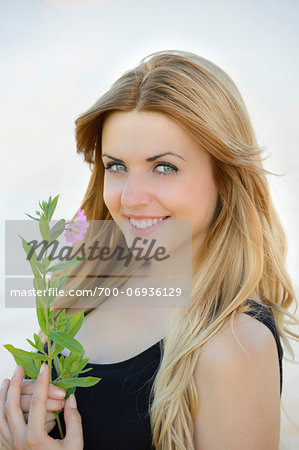 Portrait of a young woman with a flower outdoors in summer, Germany Stock Photo - Rights-Managed, Image code: 700-06936129