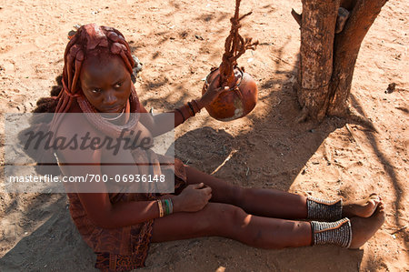 Himba woman making butter in a dried pumpkin, Kaokoveld, Namibia, Africa Stock Photo - Rights-Managed, Image code: 700-06936148