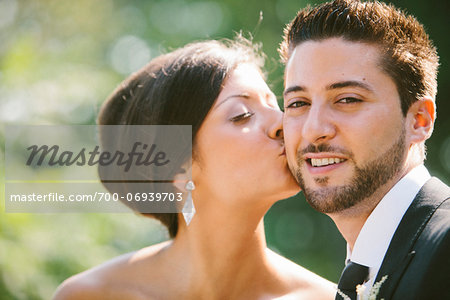 Close-up, outdoor portrait of Bride kissing Groom on cheek Stock Photo - Rights-Managed, Image code: 700-06939703