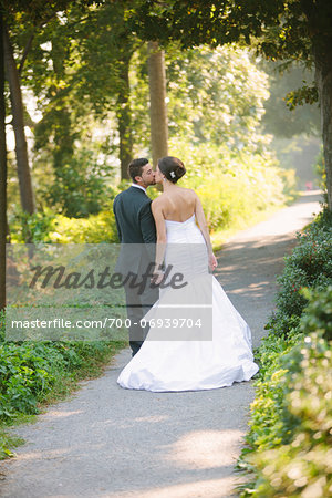 Backview of Bride and Groom kissing and holding hands, walking down pathway outdoors, on Wedding Day Stock Photo - Rights-Managed, Image code: 700-06939704