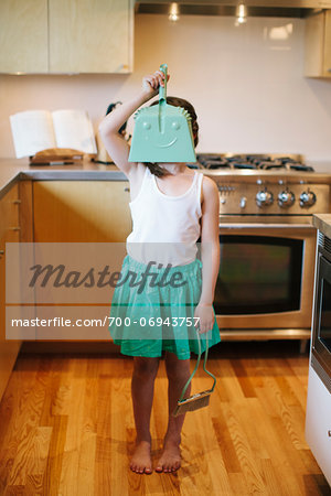 Young girl holding dustpan in front of face, standing in kitchen. Stock Photo - Rights-Managed, Image code: 700-06943757