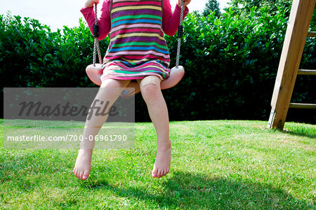 Girl sitting on a swing in backyard Stock Photo - Rights-Managed, Image code: 700-06961790