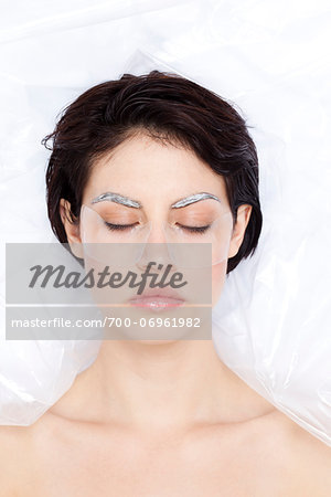 Close-up of Woman with eyes closed, wrapped in plastic, dying eyebrows, studio shot Stock Photo - Rights-Managed, Image code: 700-06961982