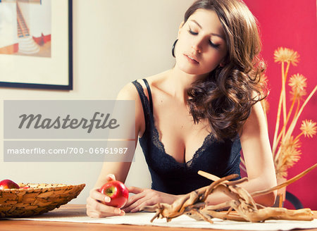 Portrait of woman in lingerie sitting at table holding apple, Germany Stock Photo - Rights-Managed, Image code: 700-06961987
