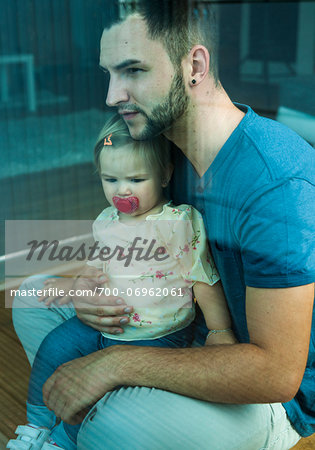 Baby Girl sitting on Father's Lap at Home, Mannheim, Baden-Wurttemberg, Germany Stock Photo - Rights-Managed, Image code: 700-06962061