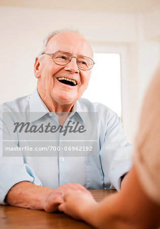 Senior Man Smiling and Talking to Young Woman at Home, Mannheim, Baden-Wurttemberg, Germany Stock Photo - Rights-Managed, Image code: 700-06962192