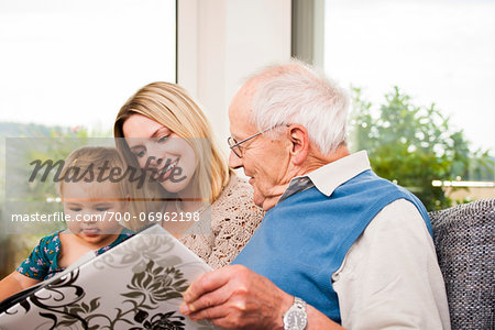 Young Woman with Baby Girl and Senior Man looking at Photo Album, Mannheim, Baden-Wurttemberg, Germany Stock Photo - Rights-Managed, Image code: 700-06962198