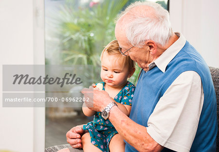 Senior Man with Baby Girl Sitting on his Lap at Home, Mannheim, Baden-Wurttemberg, Germany Stock Photo - Rights-Managed, Image code: 700-06962202