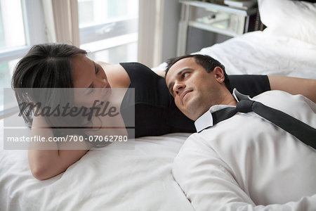Couple laying in bed wearing formal wear, looking at each other Stock Photo - Rights-Managed, Image code: 700-07062780