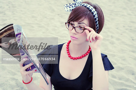 Portrait of young woman wearing horn-rimmed eyeglasses reading magazine on beach, Italy Stock Photo - Rights-Managed, Image code: 700-07066934