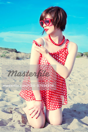 Young woman kneeling in sand on beach, wearing retro clothing, Italy Stock Photo - Rights-Managed, Image code: 700-07066938