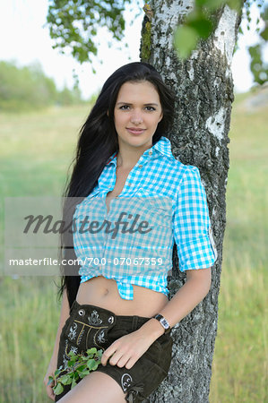 Portrait of young woman leaning against tree, Bavaria, Germany Stock Photo - Rights-Managed, Image code: 700-07067359