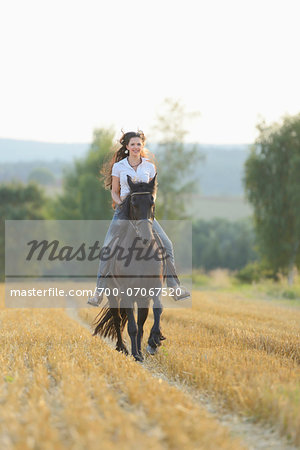 Young Woman Riding a Friesian Horse through threshed Cornfield, Bavaria, Germany Stock Photo - Rights-Managed, Image code: 700-07067520