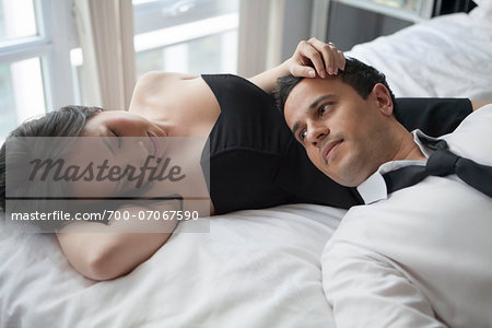 Couple laying on bed in formal wear, looking at each other Stock Photo - Rights-Managed, Image code: 700-07067590