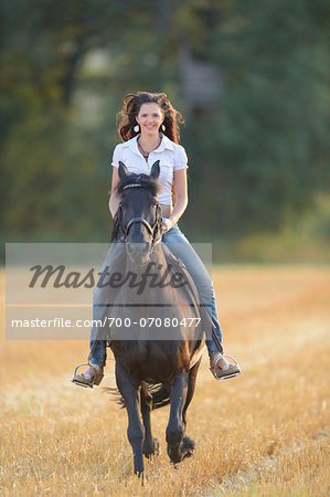 Portrait of young woman riding a Friesian horse in a cut cornfield, Bavaria, Germany Stock Photo - Rights-Managed, Image code: 700-07080477