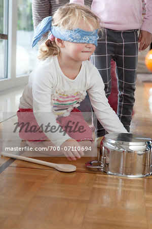Girl Sitting on Floor with Blindfold Playing Hit the Pot, Mulheim, North Rhine-Westphalia, Germany Stock Photo - Rights-Managed, Image code: 700-07110694