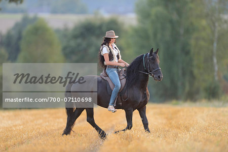 Young Woman Riding Friesian Horse on threshed Cornfield, Bavaria, Germany Stock Photo - Rights-Managed, Image code: 700-07110698