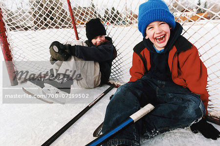 Portrait of Two Boys Sitting in Hockey Net at Outdoor Ice Rink Stock Photo - Rights-Managed, Image code: 700-07199502