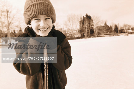 Boy Leaning on Hockey Stick Outdoors Stock Photo - Rights-Managed, Image code: 700-07199507