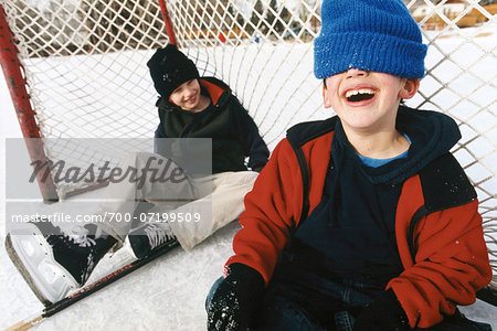 Two Boys Sitting in Hockey Net on Outdoor Ice Rink, Laughing Stock Photo - Rights-Managed, Image code: 700-07199509