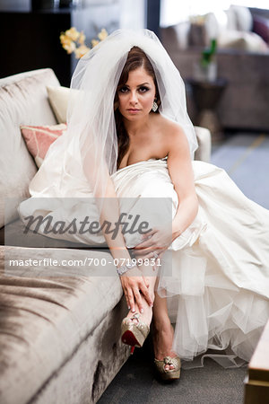 Portrait of bride sitting on sofa wearing wedding gown and veil, Ontario, Canada Stock Photo - Rights-Managed, Image code: 700-07199831