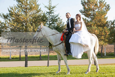 Bride and groom riding white horse together on wedding day, Ontario, Canada Stock Photo - Rights-Managed, Image code: 700-07199863