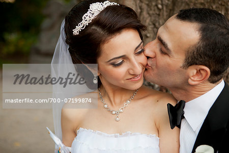 Close-up portrait of groom kissing bride on cheek, outdoors in Autumn, Ontario, Canada Stock Photo - Rights-Managed, Image code: 700-07199874
