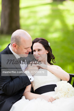 Portrait of bride and groom sitting outdoors in garden, holding hand, smiling and looking at each other, Ontario, Canada Stock Photo - Rights-Managed, Image code: 700-07199878