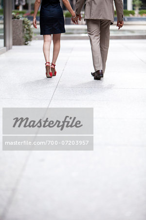 Backview of couple walking hand-in-hand down sidewalk on city street, Toronto, Ontario, Canada Stock Photo - Rights-Managed, Image code: 700-07203957