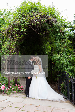Bride and Groom standing outdoors under arbour, kissing on Wedding Day, Canada Stock Photo - Rights-Managed, Image code: 700-07232326
