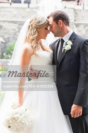 Portrait of Bride and Groom standing face-to-face outdoors with arms around each other on Wedding Day, Canada Stock Photo - Rights-Managed, Image code: 700-07232330
