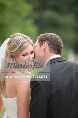 Close-up of Groom kissing Bride on cheek on Wedding Day outdoors, Canada Stock Photo - Rights-Managed, Image code: 700-07232333