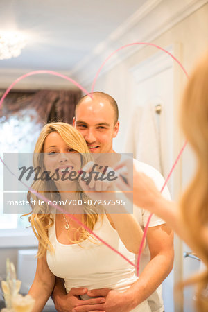 Young couple embracing and looking in bathroom mirror together, drawing a heart with lipstick on mirror, Canada Stock Photo - Rights-Managed, Image code: 700-07237595