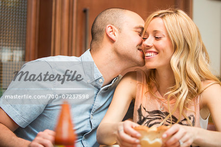 Young man kissing young woman on cheek, sitting and eating in home, Canada Stock Photo - Rights-Managed, Image code: 700-07237598