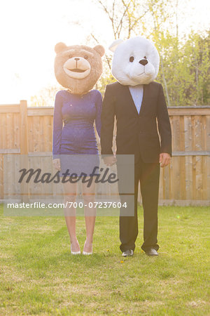 Portrait of couple standing in backyard dressed in formal attire, covering faces wearing costume bear heads, Canada Stock Photo - Rights-Managed, Image code: 700-07237604