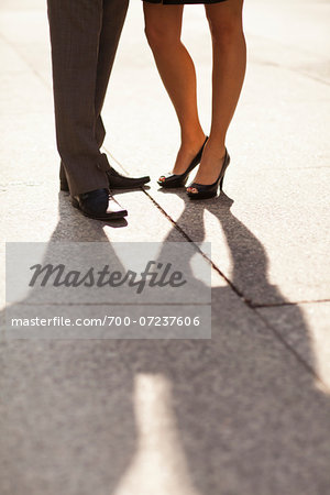 Close-up of young couples legs and feet with shadows, wearing dress shoes and standing on sidewalk, Canada Stock Photo - Rights-Managed, Image code: 700-07237606